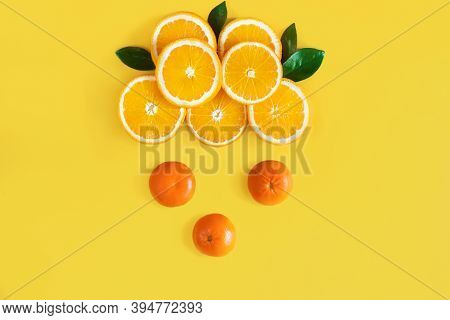 Cloud Is Laid Out Of Slices Of Juicy Oranges, Tangerines, Is In Center Of Yellow Background. Summer