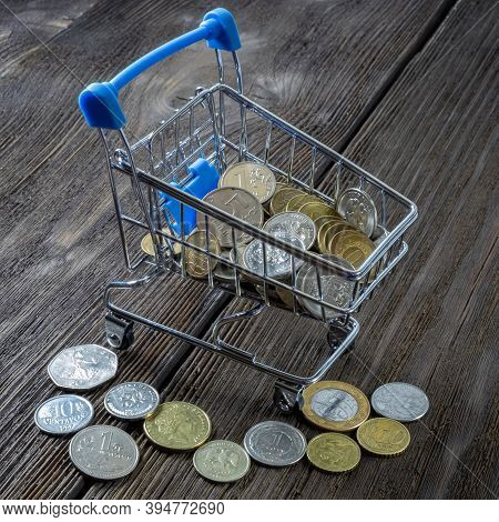 A Shopping Cart Filled With Coins Of Various Denominations. International Crisis; Abstraction Of Cur