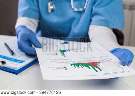 Doctor Wearing Protective Gloves Holding Document Chart,analyzing Covid-19 Graph Data,coronavirus Gl