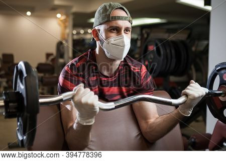 Young Caucasian Man Working Out In An Indoor Gym, Barbell Bicep Curl Exercise, Wearing Protective Fa