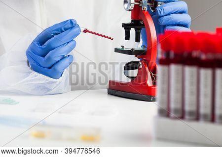 Medical Technologist Or Lab Scientist Examining Coronavirus Patient Specimen,placing Blood Sample Un