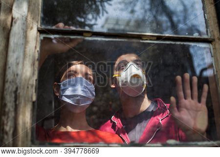 Family Quaranteaming,young Caucasian Couple Wearing Protective Medical Masks Looking Through The Win