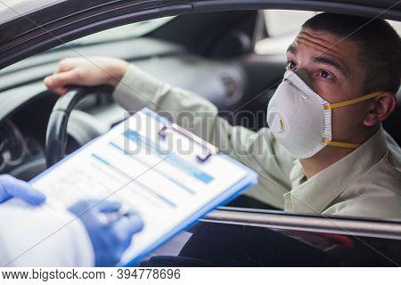 Young Man Wearing Protective Face Mask In Drive-thru Coronavirus Car Testing Center,answering Health