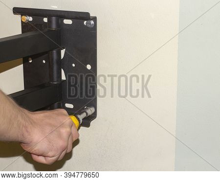 Attaching Of The Mount To The Wall By Screwdriver.