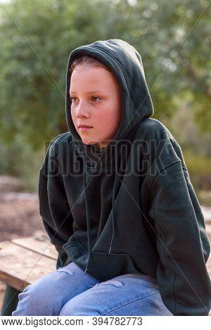 Tween Beautiful Girl In A Hoodie. Portrait Of A Pensive Dreamer Teenage Girl Wearing Green Hoodie Si