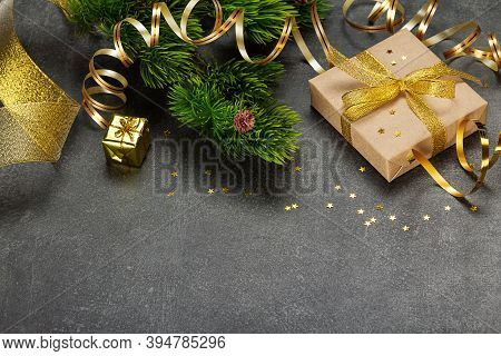 Branch Of Christmas Tree Decorated With A Golden Serpentine, Gifts With A Beautiful Ribbon And Confe