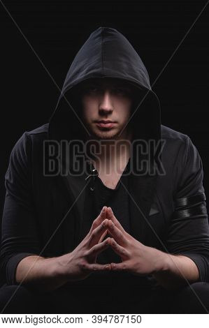 A Large Man In A Hood And A Black Sweater With Hands In A Gesture Of Strength. Studio Portrait With