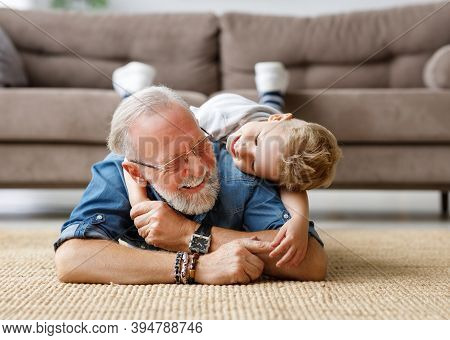 Happy Family: Delighted Boy  Embracing Elderly Grandfather From Behind And Looking At Camera While L