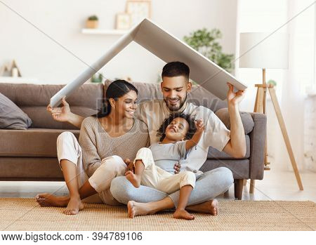 Delighted Diverse Parents And Mixed Race Son Sitting Under Roof And Smiling Near Sofa In Cozy Living