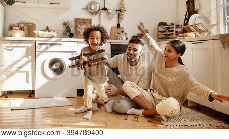 Happy Multi Ethnic Family: Little Boy Laughing And Playing With   Toy Airplane In Front Of His  His