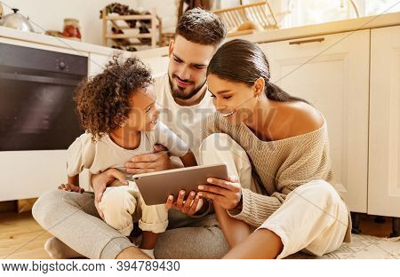 Happy Multi Ethnic Family: Parents And Little Son Watching Cartoon On Tablet On Weekend Day  While S