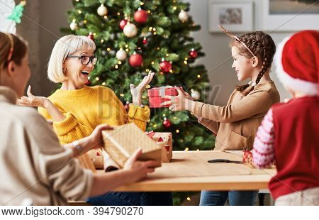 A Happy Multi Generation Family Grandmother, Mother And Children  Pack Christmas Gifts At Home Near