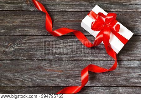 Gift Box With Red Ribbon On A Wooden Background. Concept Holiday. Greetings Card On Happy Mother's D