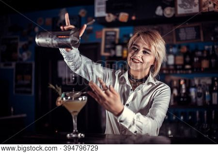 Pretty Girl Bartender Adds Ingredients To A Cocktail Behind Bar