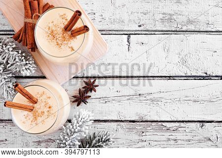 Spiced Christmas Eggnog. Top View Side Border With Copy Space On A Rustic White Wood Background.