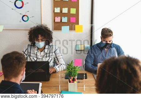Young People In Co-working Creative Space Wearing Surgical Mask And Keeping Social Distance To Avoid