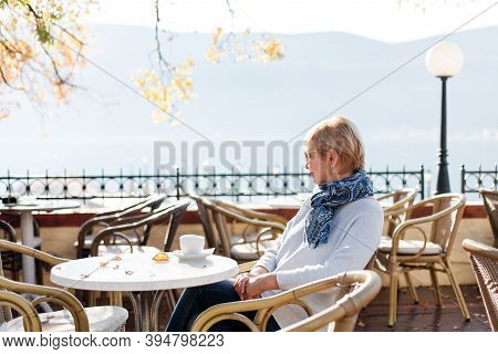 Happy Senior Woman In Cozy Autumn Cafe Outdoors. Retired Stylish Lady Drinking Morning Coffee And En