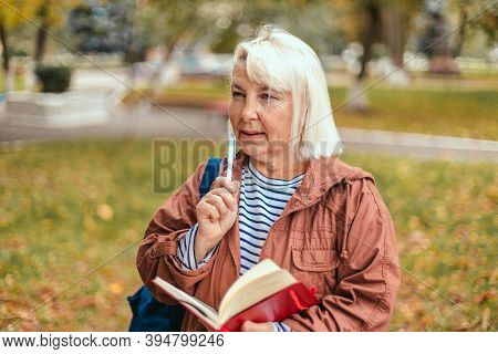 Portrait Of Thoughtful Concentrated Busy Senior Woman Having Notepad And Pen In Hands Planning, Expe