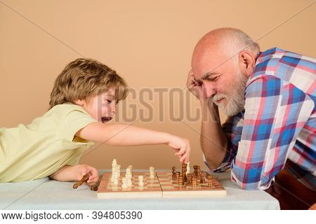 Playing Chess. Kid Playing Chess With Grandpa. Grandfather And Grandson Play Chess. Family Relations
