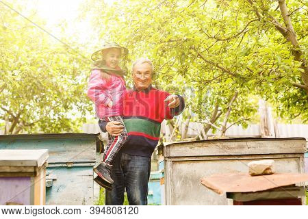 An Experienced Beekeeper Transfers Knowledge Of Beekeeping To A Small Beekeeper. The Concept Of Tran