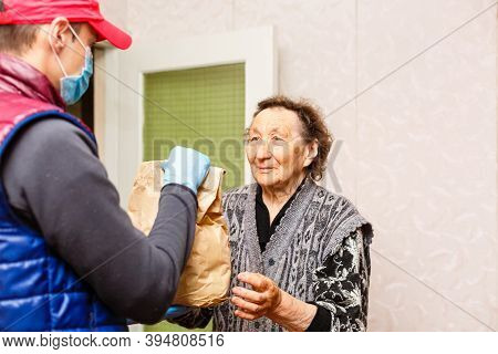 An Elderly Woman Stays At Home. Food Delivery In A Medical Mask To The Elderly.