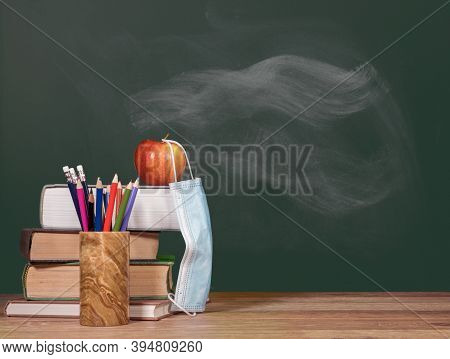 Concept For Back To School With Coronavirus Or Covid-19 With Books And Apple Against A Chalkboard Wi