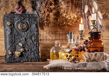 Spell Book, Magic Potion And Dried Herbs On The Witch Table Concept.