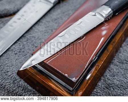 Selective Focus On The Blade Of A Steel Kitchen Knife Lying On A Water Whetstone. The Process Of Sha