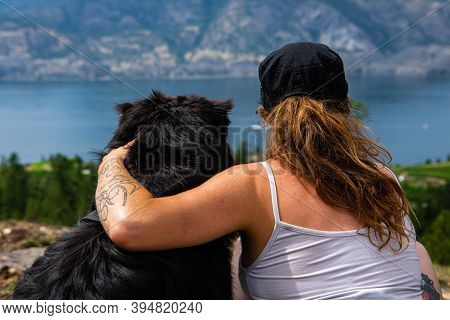 Rear View Close Up Shot Of A Woman, With Her Arm Over The Shoulders Of Her Dog While They Both Admir