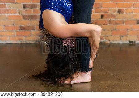 A Closeup Shot Of A Flexible Woman During An Advanced Vinyasa Flow Yoga Workout, Bent Forward In A S
