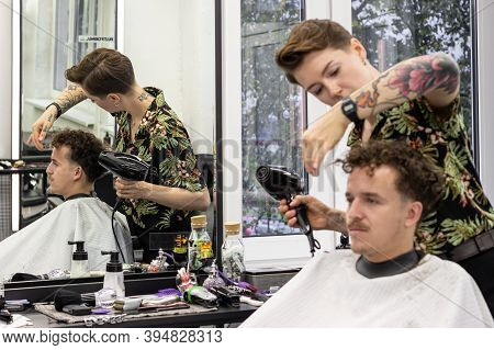 Minsk, Belarus - October 14, 2020: Tattooed Barber Gently And Gently Blow-dry Hair Of Visitor.