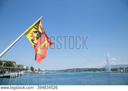 Flag Of The Geneva Canton In The City Center Of Geneva, On The Leman Lake. The Iconic Jet D'eau (wat