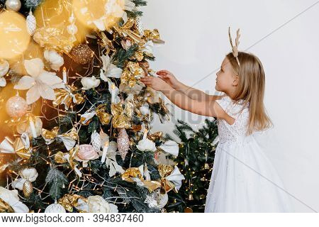 A Five-year-old Girl Is Decorating A Christmas Tree. Children, Family And Holiday Concept. Christmas