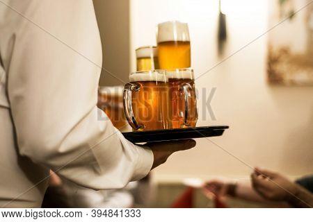 Different Beer Drinks On A Plate Served By Waiter In A German Biergarten Beergarden