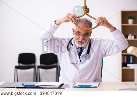 Old male doctor committing suicide at workplace