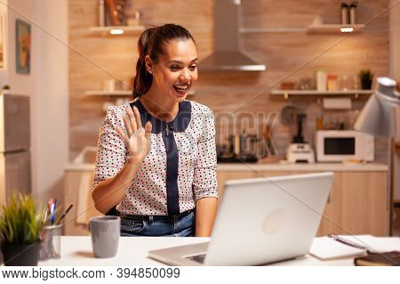 Businesswoman Waving During Video Conference While Working From Home At Night. Employee Using Modern