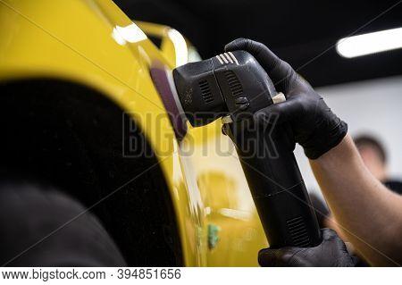 Man Car Detailing Studio Worker Polishing Yellow Car Varnish With Electrical Polisher
