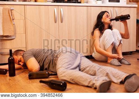 Abbused Wife Drinking Alcohol After Being Brutally Beaten By Agressive Husband In Kitchen. Alcoholic