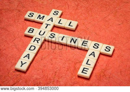 small business Saturday - crossword against handmade mulberry paper, holiday shopping concept