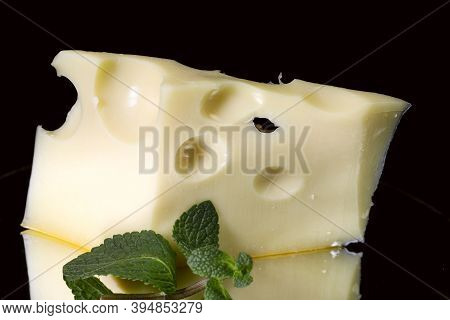 A Piece Of Medium Hard Cheese With Round Holes On A Black Background. Reflection Of A Piece Of Chees