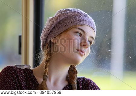 Portrait Of A Young Dreamy Freckled Girl With Pigtails Dressed In Retro Style Clothes In A Wagon Of