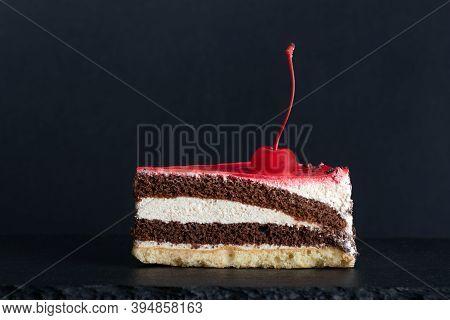 Piece Of Chocolate Vanilla Sponge Cake With Maraschino Cherry. Black Background. Side View.