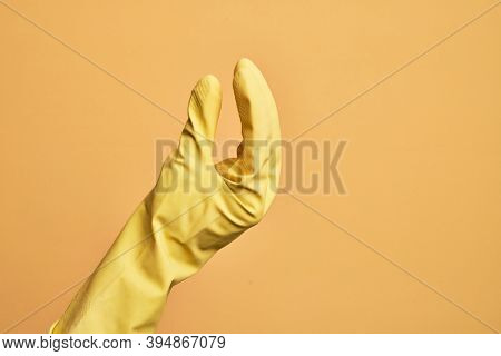 Hand of caucasian young man with cleaning glove over isolated yellow background picking and taking invisible thing, holding object with fingers showing space