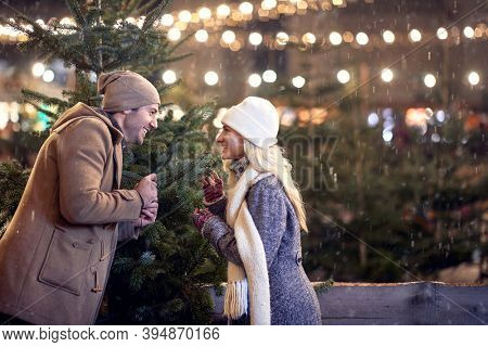 A young cheerful couple looking for a perfect christmas tree in a magical night on a snowy weather in the city. Christmas tree, love, relationship, Xmas, snow