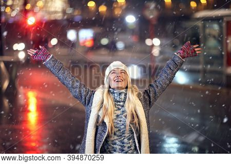a woman with raised hands enjoy a winter snowy night; Winter snow joy concept