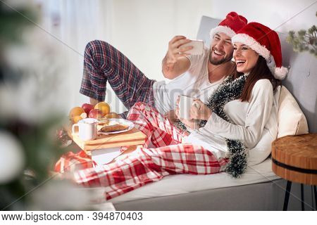 Joyful couple together in a bed on a Christmas morning