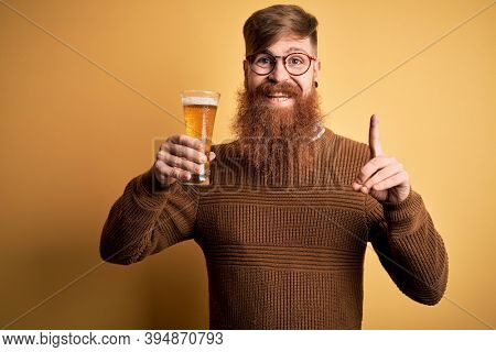 Irish redhead man with beard drinking a glass of refreshing beer over yellow background surprised with an idea or question pointing finger with happy face, number one