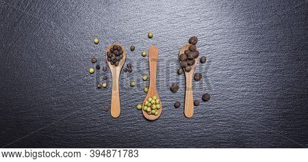 Green Pepper, Allspice Peas And Whole Mix Peppercorns, Pepper Mix In Wooden Spoons On Dark Backgroun