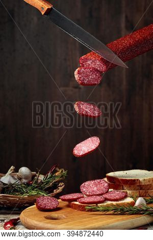 Sandwich With Salami On A Cutting Board. Sliced Sausage With Rosemary, Red Pepper, And Garlic On An