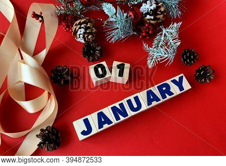 January 1 On Wooden Cubes.near Fir Branches, Cones, Ribbon, Gift Box On A Red Background.beginning O